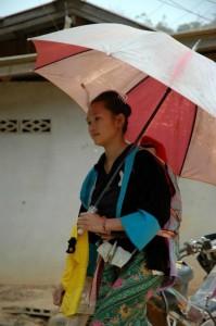Kvinde med parasol og barn på ryggen