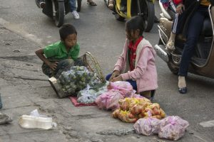 Fattige børn i Kon Tum sælger frugt til folk på scooter
